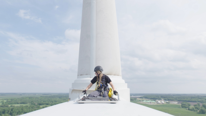 Faith Lutat, wind school student, looks out from the top of a wind turbine in Iowa. Credit - Nick Midwig.